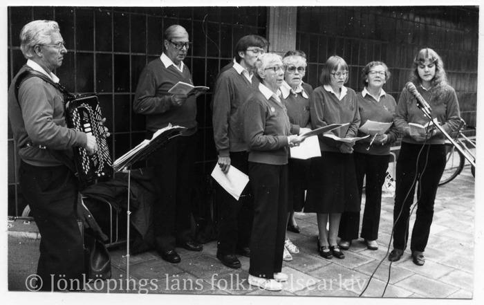 10 stycken personer står med häften och sjunger utomhus framför en mikrofon. En av dem spelar dragspel.