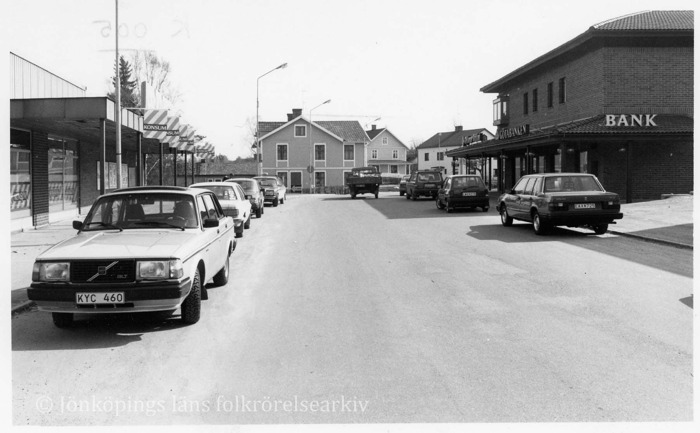 Foto på gata kantad av bilar. På ena sidan en Konsumbutik, på den andra sidan en bank.