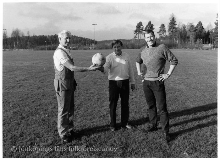 Tre män stående på fotbollsplan. Två av dem håller gemensamt upp en fotboll.