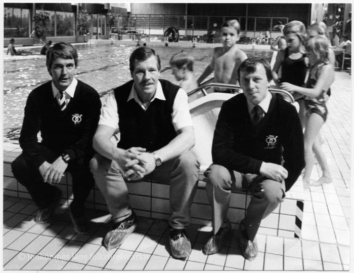 Tre män sitter vid kanten av en simbassäng. I bakgrunden lekande barn.