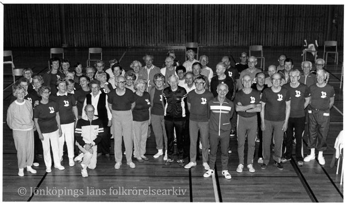 Ett femtiotal äldre människor stående i en gymnastiksal.