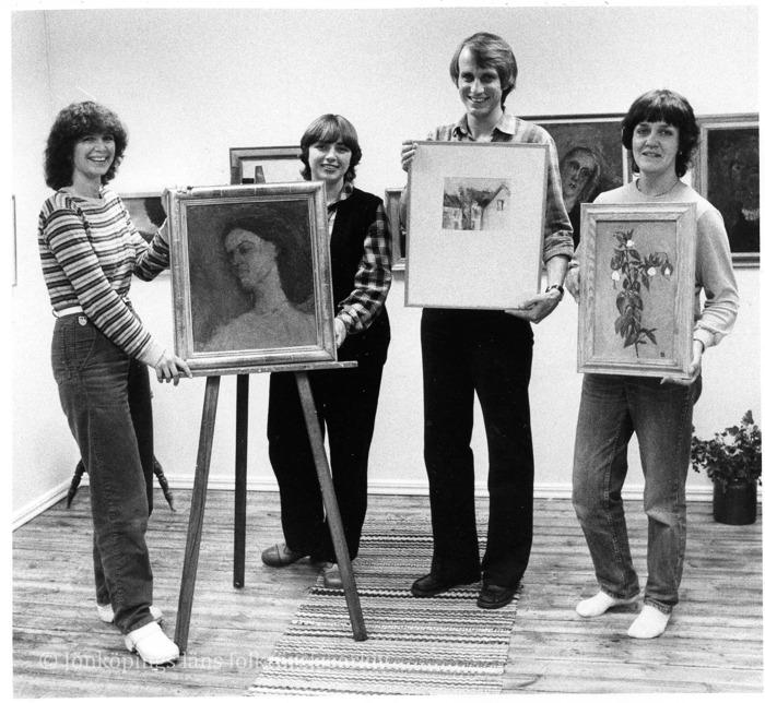 Foto på tre kvinnor och en man som står i ett rum och håller upp tavlor.