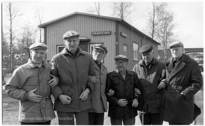 Foto på sex äldre män som står framför ett trähus.