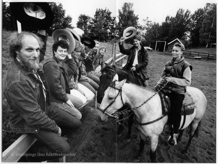 Foto på sex män och kvinnor som sitter på ett staket. De håller upp sina cowboy-hattar i luften. Vid staket en man och kvinna som sitter på varsin häst.