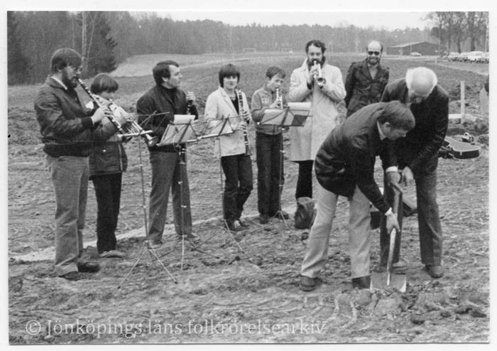 Foto på två män som gemensamt tar ett spadtag i marken. I bakgrunden sex personer som spelar olika blåsinstrument.