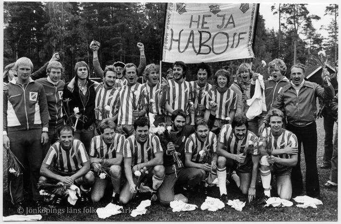 """Foto på runt tjugo män i fotbollströjor eller träningskläder som håller upp blommor och en banderoll med texten """"Heja Habo IF""""."""