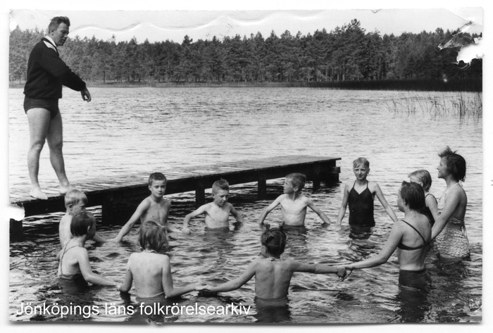 Foto på en grupp med pojkar och flickor som har bildat en handhållen ring i vattnet vid en brygga. På bryggan står en man och ger instruktioner. I bakgrunden skog.