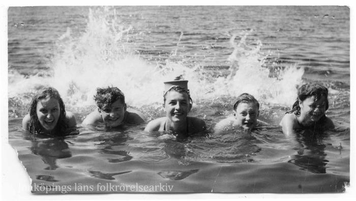 Foto på fem ungdomar, både pojkar och flickor, som simmar i bredd mot kameran. Vatten stänker upp vid deras fötter.