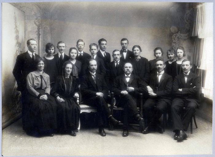 Ataljéfoto på ett tjugotal finklädda män och kvinnor. Några står och några sitter.