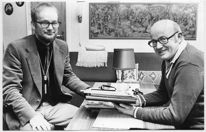 Foto på två män som sitter vid ett bord med ett par böcker framför sig. I bakgrunden en soffa och en väggbonad. Båda ler in i kameran.