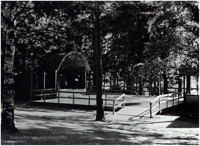 Foto på öppen dansbana med en liten scen med tak. Dansbanan är omgiven av träd.