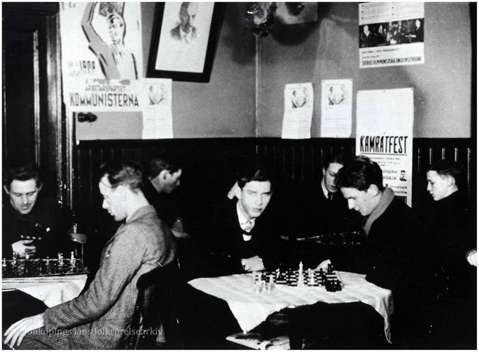 Foto på åtta män vid små runda bord som spelar schack i en lokal med bröstpanel. Ovanför panelen sitter affischer och även en tavla på Lenin.