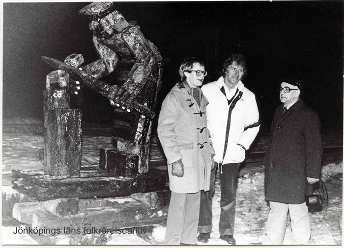 Foto på tre men vid en träskulptur föreställande en smed. Himlen är mörk och marken är täckt av snö.