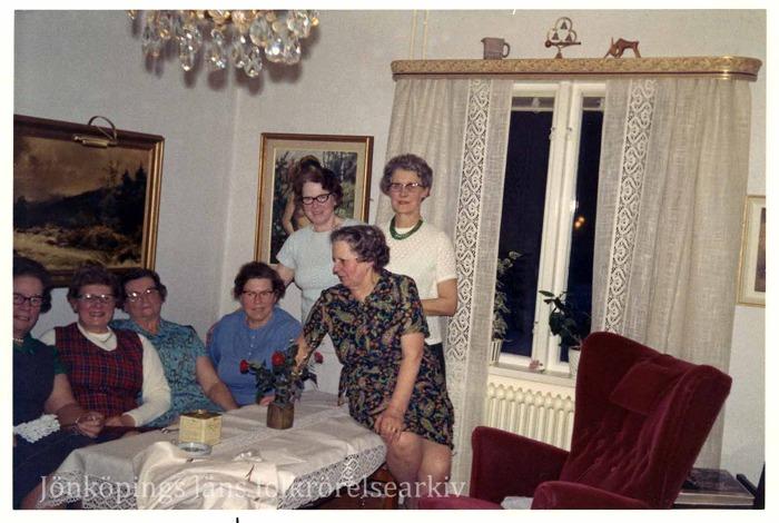 Färgfoto på sju kvinnor i vad som förefaller vara ett vardagsrum. Fyra sitter i en soffa, två står och en sitter på ett bord. I bakgrunden ett fönster med spetsgardiner. Krukväxter står på fönsterkarm