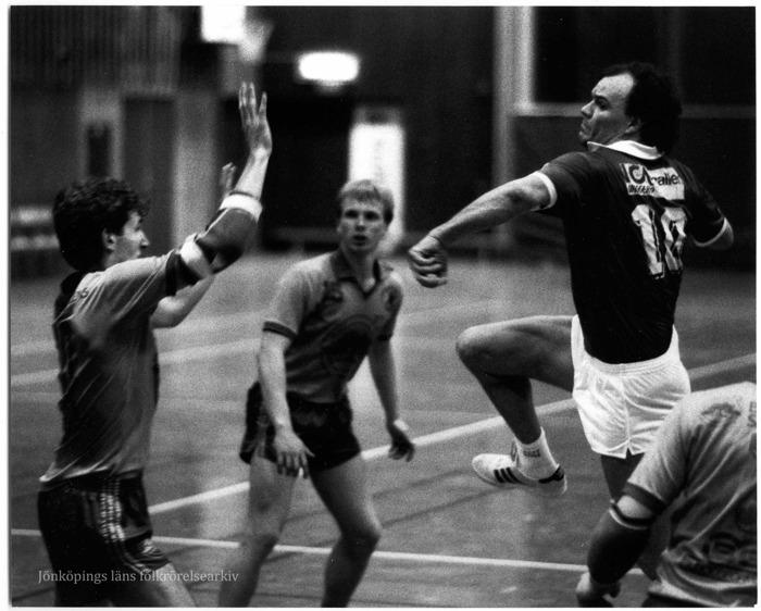 Foto på fyra handbollsspelar inbegripna i närkamp. En av dem hoppar och förbereder ett skott mot mål och en målvakt med uppsträckta händer.