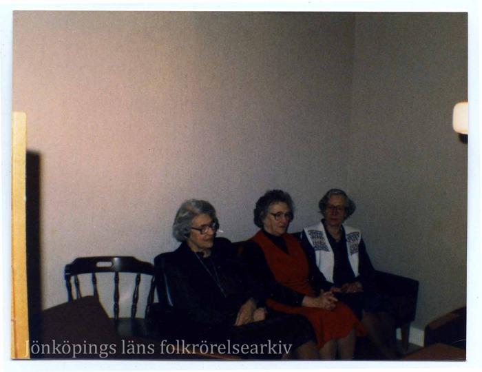 Färgfoto på tre äldre kvinnor sittande i en soffa.