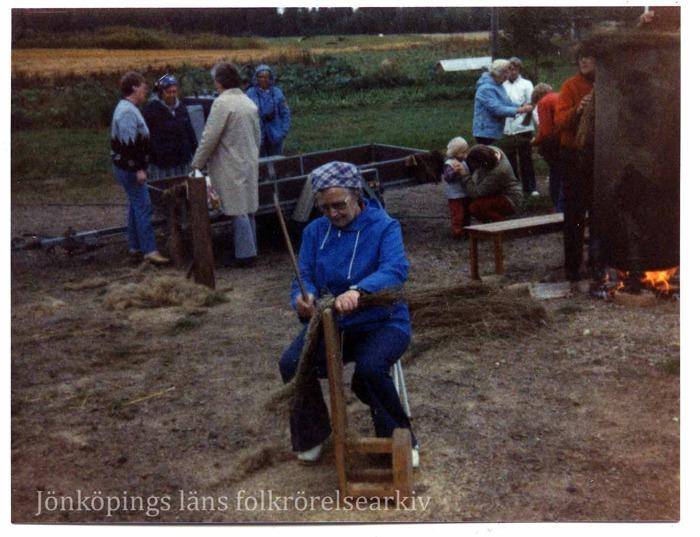 Färfoto på kvinna sittande på en pall med ett träredskap framför sig på vilket hon bereder lin. I bakgrunden människor som umgås. En eld brinner under en stor cylinder av något slag.