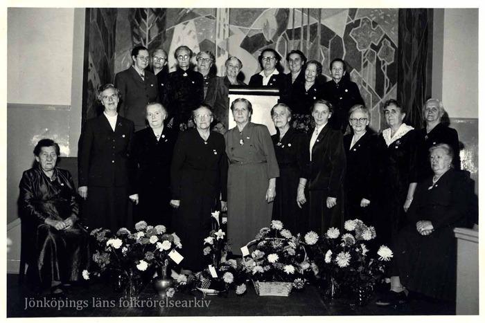Foto på ett tjugotal uppklädda kvinnor på någon slags scen. I bakgrunden en stor målning. I förgrunden flera blomsterarrangemang.