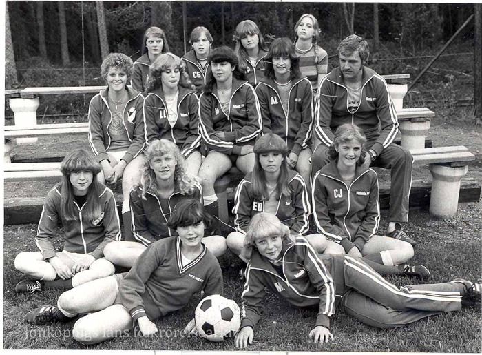 Foto på fjorton unga damer i fotbollskläder och en medelålders man som förefaller vara lagets tränare. I bakgrunden skog.