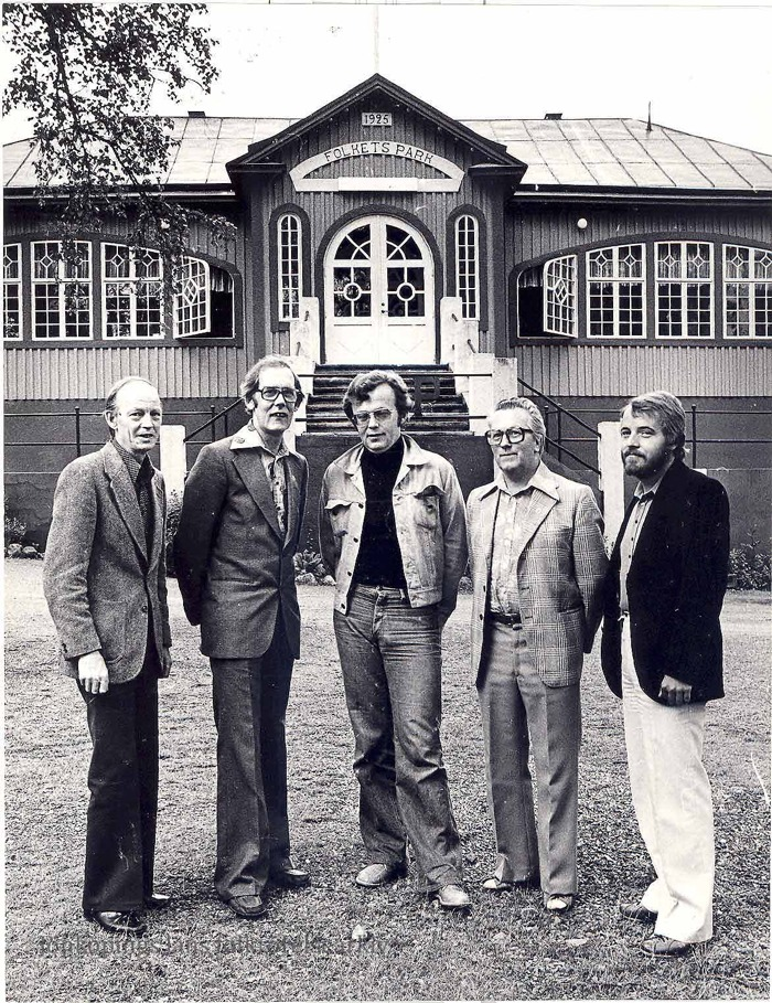 """Foto på fem män uppställda för foto framför ett trähus med rikt utsmyckade fönster. På byggnaden sitter en skylt med texten: """"1925 Folkets Park""""."""