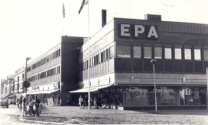 """Foto på centrumgata där ett antal människor går och cyklar. Även en tegelbyggnad med stor skylt på fasaden med texten: """"EPA""""."""
