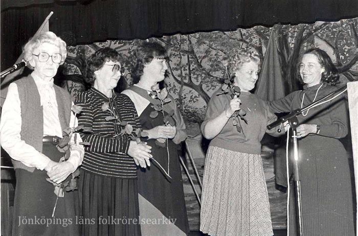 Foto på fem kvinnor på en scen vid en mikrofon. Fyra av dem håller i varsin ros.