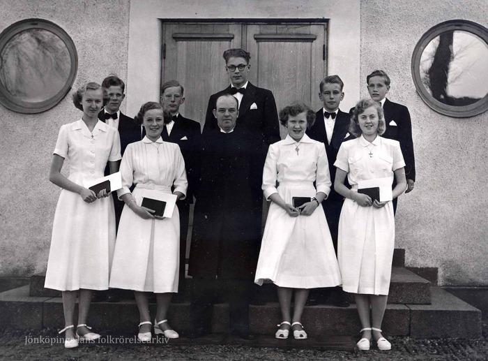 Foto på fem pojkar i svarta kostymer och fyra flickor i vita klänningar som står vid en stentrappa framför en trädörr. Mitt i gruppen står en medelålders man med prästkläder.
