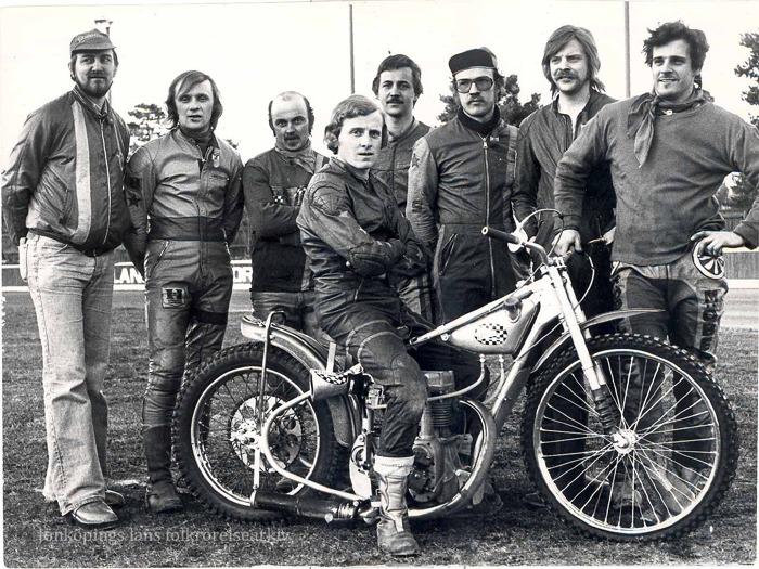 Foto på sju män uppställda på rad. Framför dem sitter en man i skinnställ på en speedway-motorcykel.