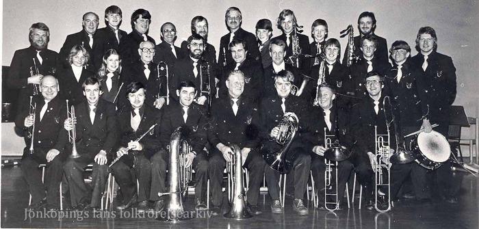 Foto på ett trettiotal män i enhetliga kläder med olika instrument.