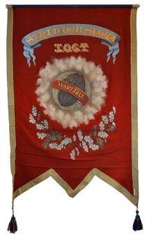 """Röd baksida på standar tillhörande Logen Ragnar Kämpe. Längst upp i en banderoll texten """"Strid och segra"""". Under denna texten """"I.O.G.T"""". I mitten en jordglob med texten """"Vårt fält""""."""