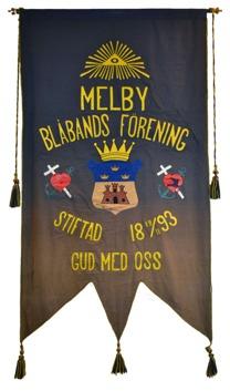 """Blå standar med gul text: """"Melby Blåbands Förening. Stiftad 1893. Gud med oss."""" I mitten en sköld med ett slott och tre kronor."""
