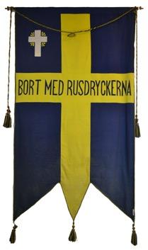 """Baksida av standar tillhörande Melby Blåbands Förening. Gult kort mot blå botten. I mitten texten: """"Bort med rusdryckerna""""."""