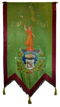 Framsida av rödgrönt standar med målade detaljer, bland annat en kvinna i klänning, jordglob och lövkrans.