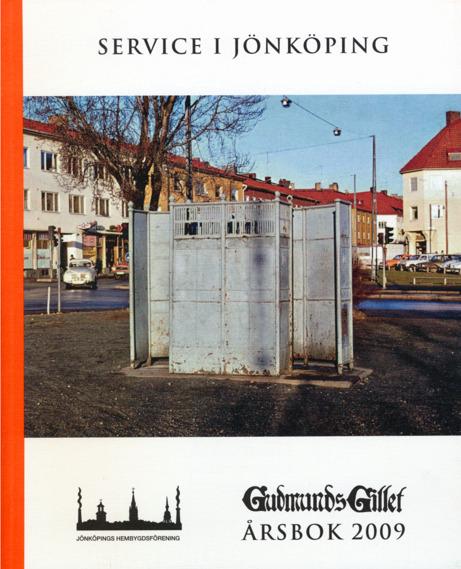 """Bokomslag till Gudmundsgillets årsbok 2009. Foto på grått metallbås utgörande en allmän urinoar eller """"pissekur"""". I bakgrunden bilar och hus."""