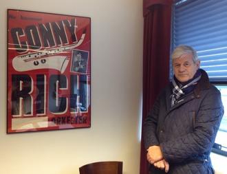 Färgfoto på stående man bredvid en inramad affisch som hänger på vägg i ett kontorsrum.
