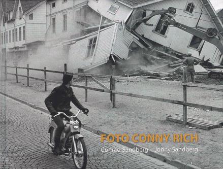 Bokomslag till boken Foto Conny Rich. Foto på man på moped som passerar ett hus som håller på att rivas med grävskopa.