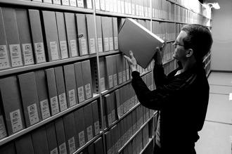 Svartvitt fotografi på folkrörelsearkivarie som ställer tillbaka en arkivkartong på en hylla.