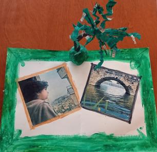 Foto av bildcollage och skulptur. Foto på ett barn som tittar ut över bebyggelse och foto på en å som rinner under en välvd stenbro. Ovanpå collaget står en skulptur av ett träd av lera och papper.