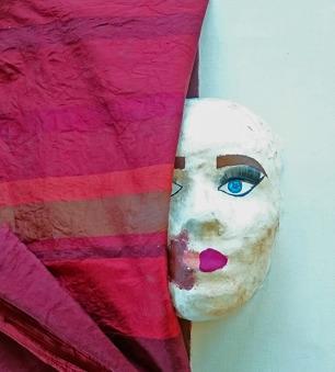Foto på tavla/skulptur av ansikte där en halvan är dold bakom tyg. Ansiktet har smink.