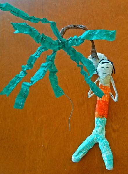Foto på skulptur av en figur som ligger med händerna bakom huvudet under ett träd.
