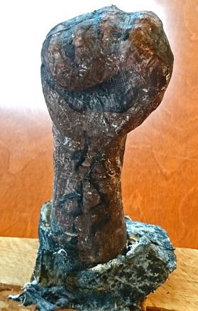 Foto på skulptur av knuten hand.