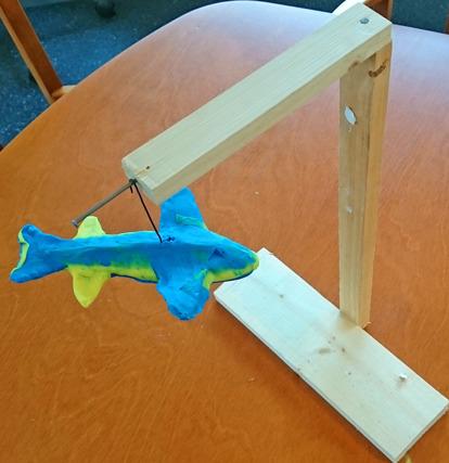Foto på staty föreställande en blågul haj som hänger i en ställning av trä.