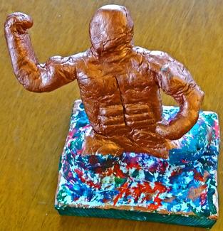 Foto på skulptur av en gyllene figur som tycks växa fram ur en mångfärgad lera.