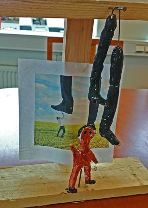 Foto på staty av en liten person som blir trampad på. I bakgrunden sitter även ett foto som illustrerar detta.