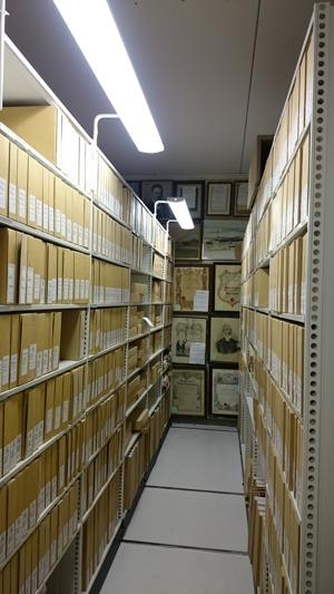 Eldrivet arkivhyllsystem med arkivkapslar. Vägg med tavlor.