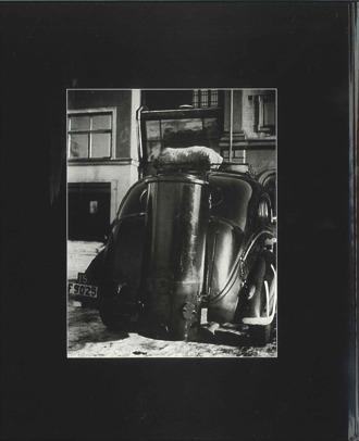 Baksidan av boken Taxi av Göran Nell. Foto på bakdelen av en gammal svart taxi.