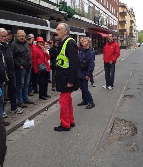 Guide talar för åhörare på gata i Jönköping. Spårvägsrälsen synlig i gatan.