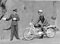 """När den uppdaterade Silverpilen presenterades med bland annat ny bensintank togs nya reklambilder. Polismannen heter Torsten Skoglund (från Huskvarnapolisen) och """"skinnknutten"""" Karl-Åke Gustavsson. Platsen är Ådalsvägen."""