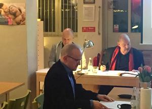 PGs omvalda ordförande Thomas W. I bakgrunden syns årsmötespresidiet i full gång.