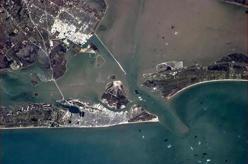 Galveston Texas har stora avrinningsområden vilket innebär att näringen ökar i vattnet utanför staden. Detta lockar till sig fiskar och hajar. Bild: NASA.